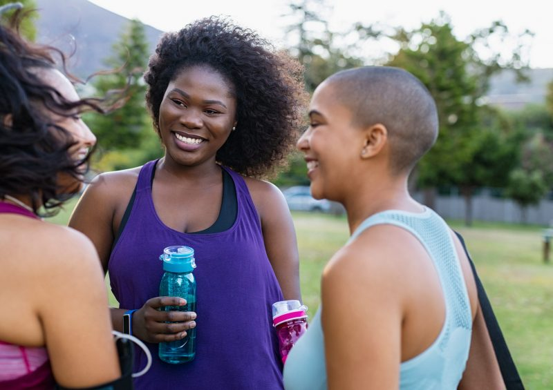 Smiling curvy girls in group chatting after yoga training in park. Three friends talking after sporty exercising outdoor. Group of active multiethnic young women talking to each other after fitness workout at park.